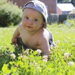 Baby wearing a cap and crawling in the grass